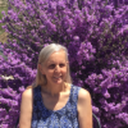 Jane of Libary Lady's Kid Lit blog headshot. She is wearing a blue tank top and standing in front of a big purple lilac bush.