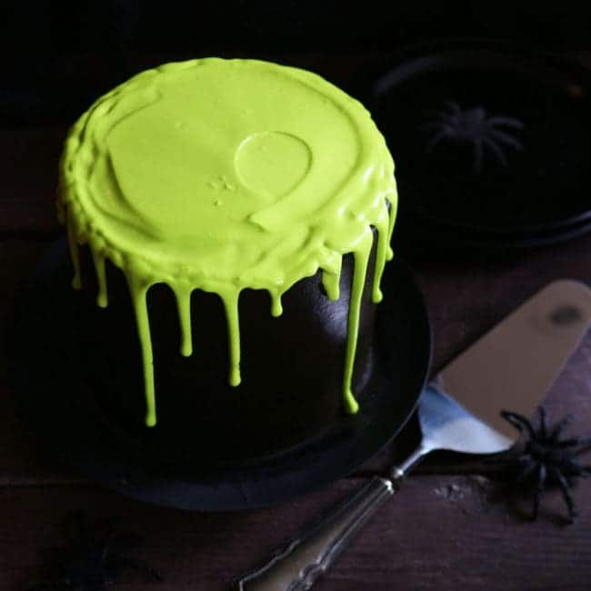 Round black layer cake with neon green slime icing on top and dripping down the sides